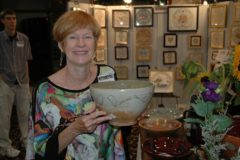 Fall for Art event chair admiring ceramic bowl